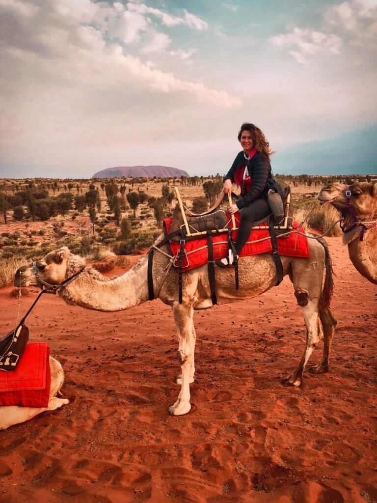 Crystal Traveler on Camel with Uluru in background.