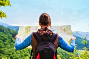 Hiking woman traveler with backpack checks map